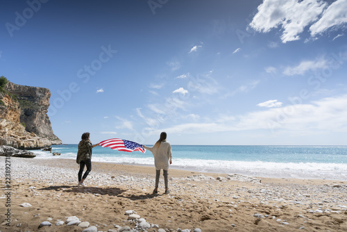 Fotografía  Two girls holding United states of America flag in beach