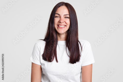 Fotografiet  Cheerful satisfied brunette lady has toothy smile, being in good mood, dressed in casual t shirt, expresses positive emotions, isolated over white background