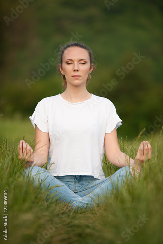 Beautiful young woman meditate on meadou na early summer evening