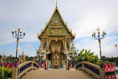 Tuinposter Bedehuis The Thai temple in Wat Plai Laem in Samui Island Thailand, in the middle of the water, contains giant statues and elephants.Pigeon flies through.