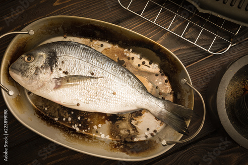 Fotografie, Obraz  Fresh dorado fish on a rustic plate with salt and pepper being prepared for cook