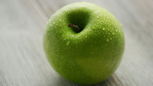 Closeup Shot Of Green Wet Apple Placed On Light Wooden Background