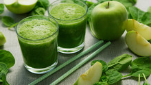 Layout Of Few Glasses Filled With Green Smoothie And Served On Table With Green Apples And Spinach Leaves