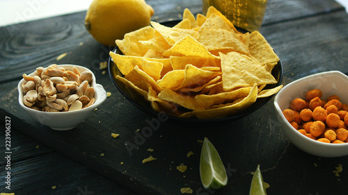 Fototapeta Snack board with served corn chips and nuts in bowls composed on wooden table for party obraz