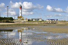 Ligthouse With Reflection On The Sand Of The Beach At Low Tide At Ouistreham , Commune In The Calvados Department In The Basse-Normandie Region In Northwestern France.