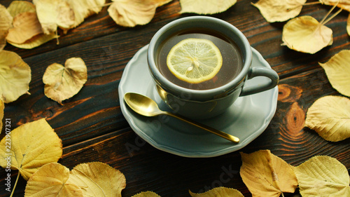 Staande foto Thee From above view of cup of hot tea with slice of lemon with saucer and spoon placed on wooden background and decorated with dry yellow leaves.