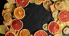 From Above Shot Of Arranged Wreath On Black Surface With Dry Leaves And Dry Citrus Slices