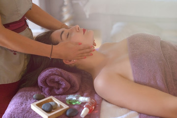 Obraz na płótnie Canvas Beautiful woman receiving massage in spa salon. Happy young beautiful girl enjoying massage at the beauty salon spa. Concept of wellness, bodycare, healthy lifestyle