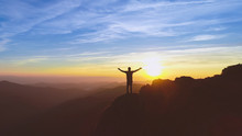 The Man Standing On The Mountain On The Picturesque Sunset Background