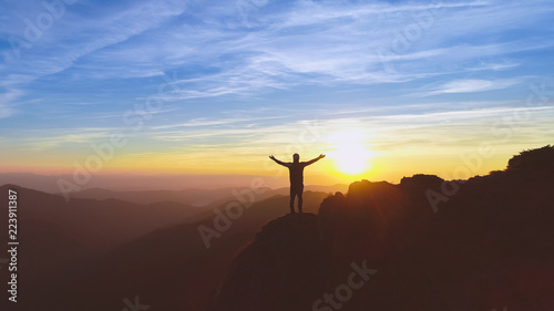 Poster Marron chocolat The man standing on the mountain on the picturesque sunset background