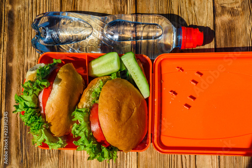 Foto op Aluminium Assortiment Hamburgers with lettuce in lunchbox and bottle of water on wooden table. Top view