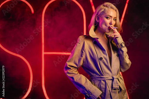 Young blondie woman smoking a cigarette wearing the beige coat Canvas Print