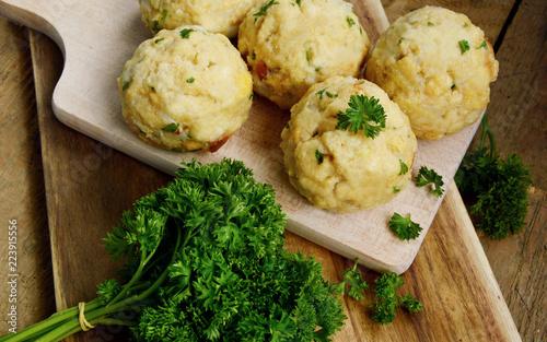 Homemade Fresh Bread dumpling.(German name is Semmelknödel) European food with wooden board and parsley.