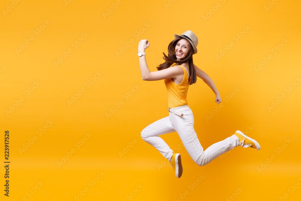 Fototapeta Portrait of excited smiling young happy jumping high woman in straw summer hat, copy space isolated on yellow orange background. People sincere emotions, passion lifestyle concept. Advertising area.