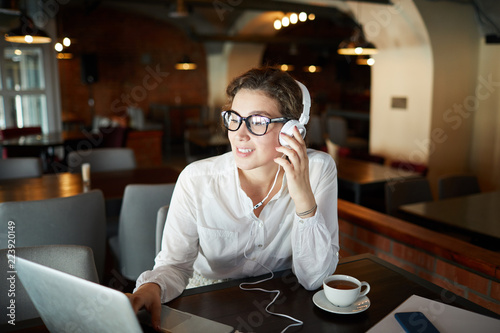 Foto  Young contemporary woman with headphones sitting in cafe in front of laptop and