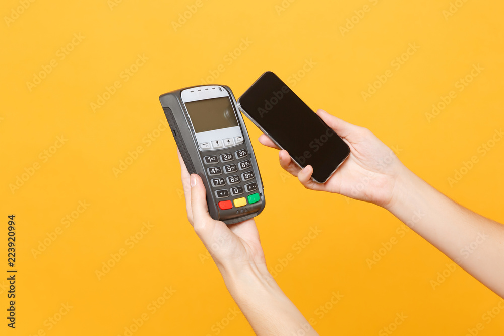 Fototapeta Close up cropped photo female holding in hands wireless modern bank payment terminal to process and acquire credit card payments mobile phone isolated on yellow background. Copy space for advertising.