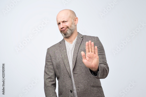 Valokuva  Attractive mature man showing refusal gesture