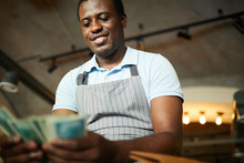 Young African-american Waiter Counting Money That He Earned For The Working Day