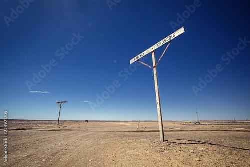 Foto op Plexiglas Oceanië Australia – Old Ghan railway crossing at the outback desert under blue sky