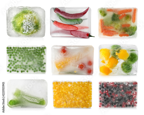 Set with vegetables and berries frozen in ice cubes on white background
