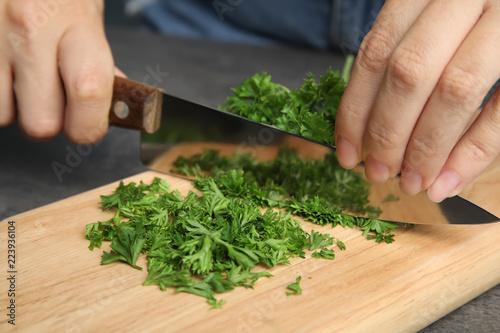 Woman cutting fresh green parsley on wooden board, closeup