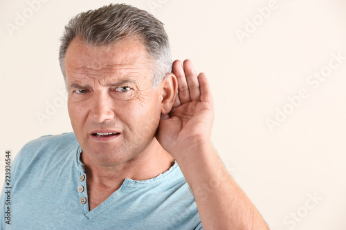 Mature man with hearing problem on light background Wallpaper Mural