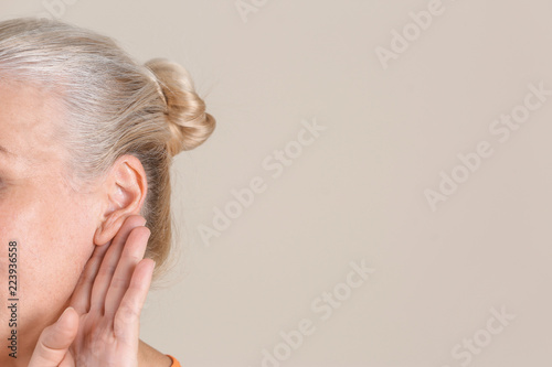 Mature woman with hearing problem on light background, closeup Canvas Print