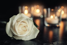 White Rose And Blurred Burning Candles On Table In Darkness, Space For Text. Funeral Symbol
