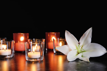White lily and burning candles on table in darkness. Funeral symbol