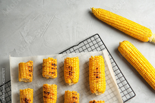 Cooling rack with grilled corn cobs on light background, top view