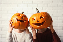 Women Holding Halloween Pumpkin Head Jack Lanterns Against Brick Wall