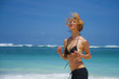young attractive and happy woman running on tropical paradise beach with white sand and vivid turquoise sea color jogging barefoot and smiling in fitness holidays