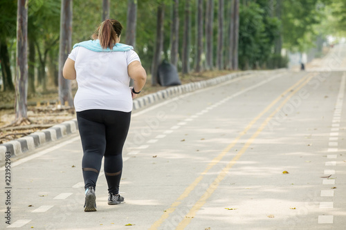 Overweight woman jogging on the road