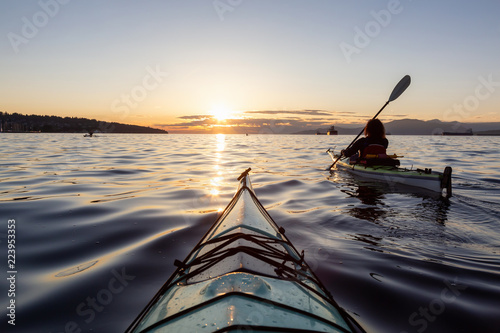 Vászonkép Girl Sea Kayaking during a vibrant sunny summer sunset