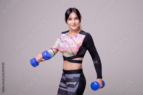 Fotografia, Obraz  Beautiful athletic woman wearing in sports style clothing makes sports exercise with dumbbells in the gym