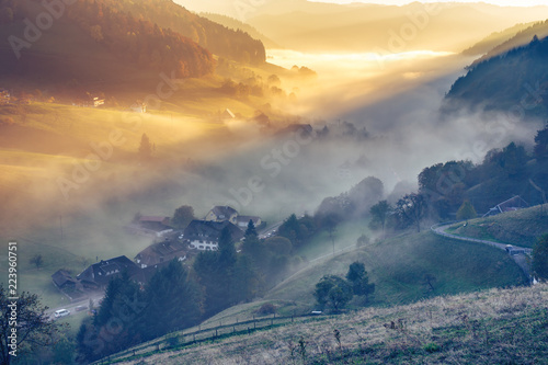 Scenic foggy mountain landscape with an old monastery in Black Forest, Germany. Colorful travel background.