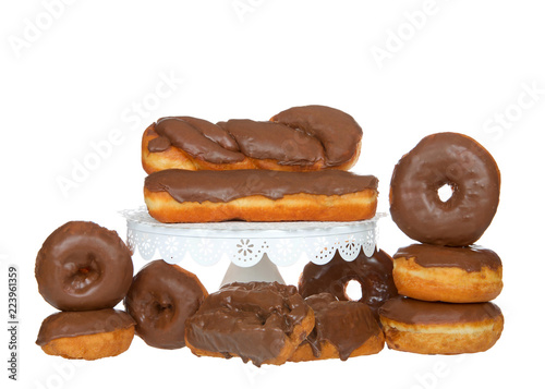 Fotografie, Obraz  Many cake donuts, glazed twist, bar and old fashioned donuts frosted in chocolate isolated on white background with some on white pedestal