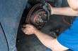 Disc brake and asbestos brake pads at car garage