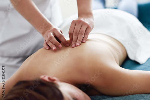 Obraz Young woman receiving a back massage by professional therapist. - fototapety do salonu