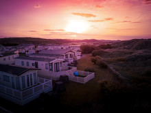 Sun Setting Over The Sea And Caravan And Camping Park, Static Home Aerial View. Porthmadog Holiday Park Taken From The Air By A Drone