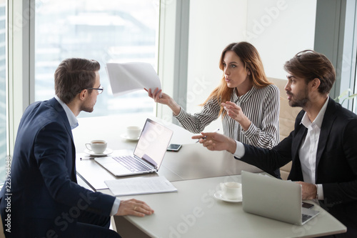 Diverse business partners disagree with company CEO on contract terms, people have dispute or fight at meeting in office, associates or colleagues argue at briefing failing cooperation or partnership