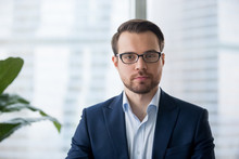 Portrait Of Serious Millennial Businessman Wearing Glasses Looking At Camera, Headshot Of Concentrated Confident Male Worker Or Director Posing In Modern Office, Making Photo Or Picture Near Window