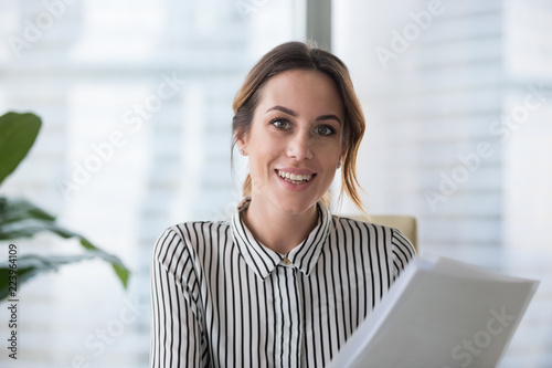 Foto Portrait of smiling millennial businesswoman holding documents looking at camera, headshot of happy woman worker or female ceo posing with paperwork making picture at corporate photoshoot