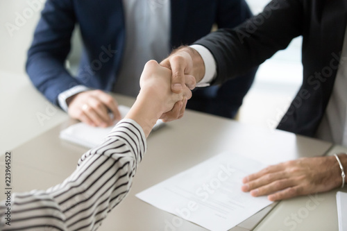 Fotografering  Close up of male recruiter shaking hand of female job applicant greeting with su