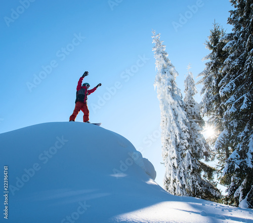 Tuinposter Wintersporten Male snowboarder freerider standing on top of the ski slope with his arms in the air in victorious gesture in the mountains copyspace recreation snowboarding extreme lifestyle sports concept.