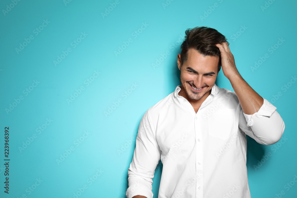 Fototapeta Young man with trendy hairstyle posing on color background