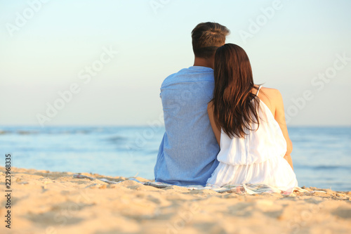 Happy young couple sitting together on beach