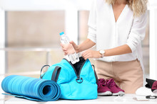 Young Businesswoman Packing Sports Stuff For Training Into Bag In Office