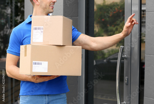 Fotografie, Obraz  Delivery service courier with parcels in hands ringing doorbell outdoors