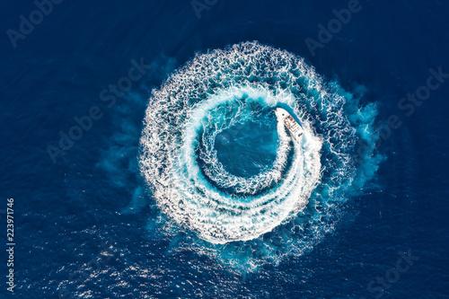 Ein Motorboot formt einen Kreis aus Luftblasen auf dem blauen Meer
